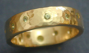 5mm wide 14kt Yellow gold hammered band. Various size peridot flush set around the band. Starting at $645
